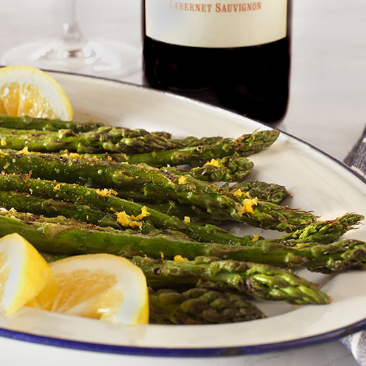 Grilled Asparagus with lemon butter on a plate paired with cabernet