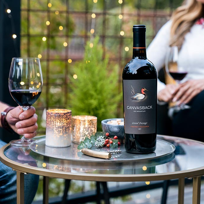 Canvasback Grand Passage Cabernet on a table with a husband and wine enjoying a glass