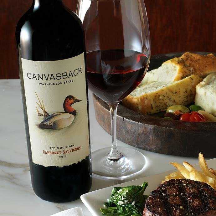 Bottle of Canvasback on table with glass and plate of food
